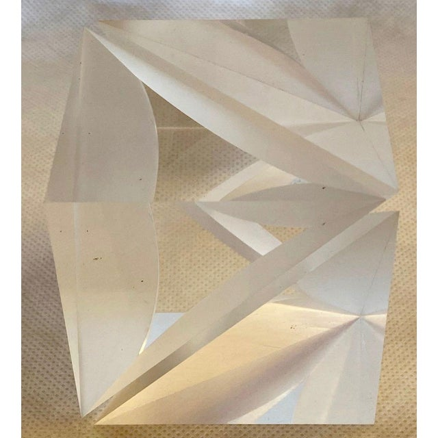 Lucite cube sculpture by Alessio Tasca for Fusina. The sculpture is a cube with a thin, curved slice cut diagonally into...