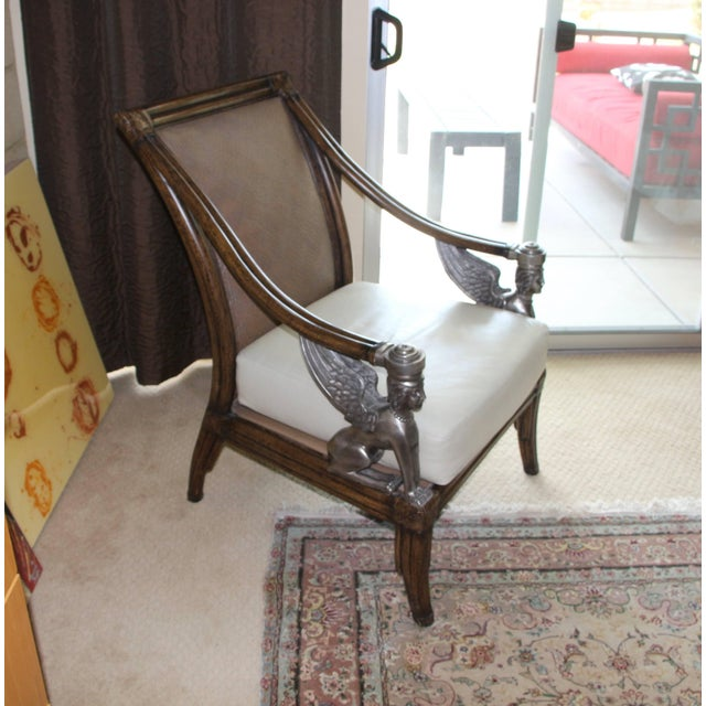 An armchair with a leather cushion seat that appears to have been recently re-upholstered. The chair made or wood, rattan...