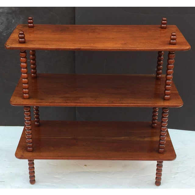A fine English rectangular console or buffet with three tiers or shelves and four bobbin turned supports of mahogany.
