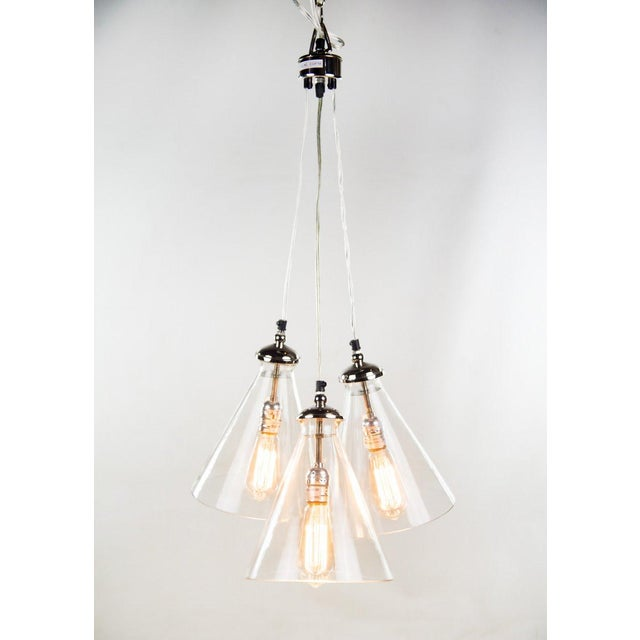 Shed some light in your bathroom, kitchen or living room with this Modern triple cone ceiling light. It has three clear...