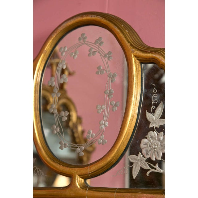 A lovely gilt wood mirror in the Hollywood Regency style, the top part with etched glass depicting floral and clover...