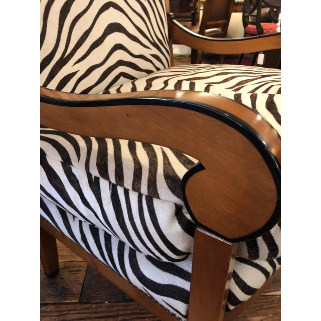 A fabulously chic oversized club chair having Biedermeieresque birdseye maple and ebonized