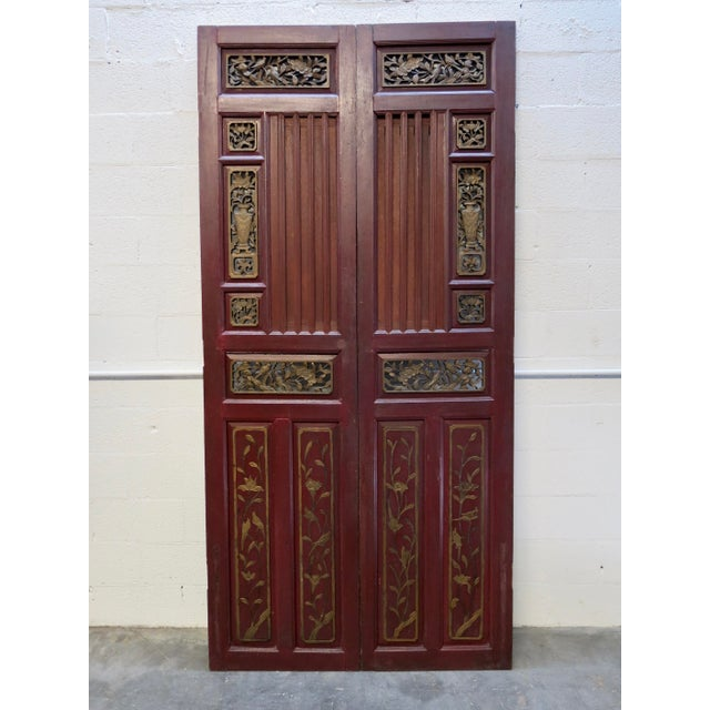 Pair of antique Chinese wooden doors with intricately hand carved and gilt panels throughout. Each door has a sliding...