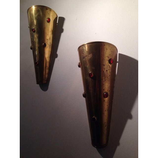 Wired for European (candelabra) socket and red cabochon stones that let light through on these brass half cone wall sconces.