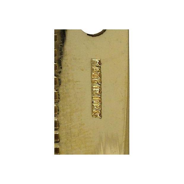 "Judith Leiber brass hair comb with original gold tassel. Marked ""Judith Leiber"" and ""Made in Italy."" Light oxidation; such..."