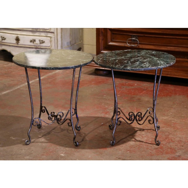 Decorate a covered patio with this elegant pair of side tables. Crafted in France circa 1960, each forged iron base stands...