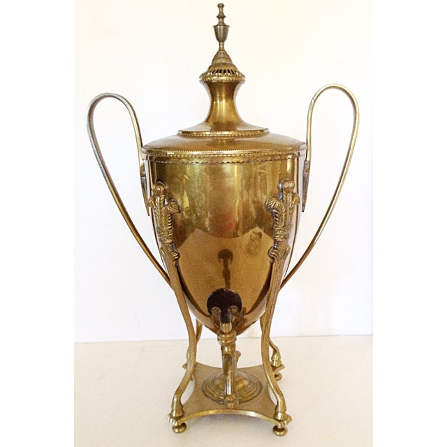 This elegant serving urn is made of brass on the outside and lined with tin. It is in the design of a trophy with tall...
