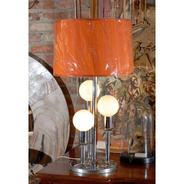 Mid-Century Modern lamp of chrome over three graduated round frosted bulbs on a platform base. Lampshade not included in...