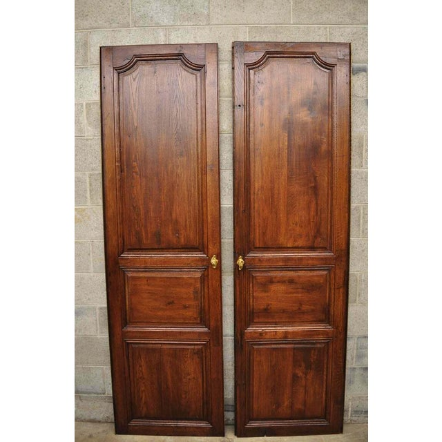 Pair of antique French Louis XVI style carved oak interior double doors with bronze rococo door knobs (B) Circa 19th...