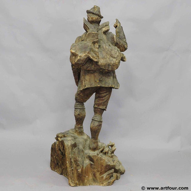 a unfinished handcarved poacher statue. a poacher on the way back from the hunt with a hunted ibex gun on the back....