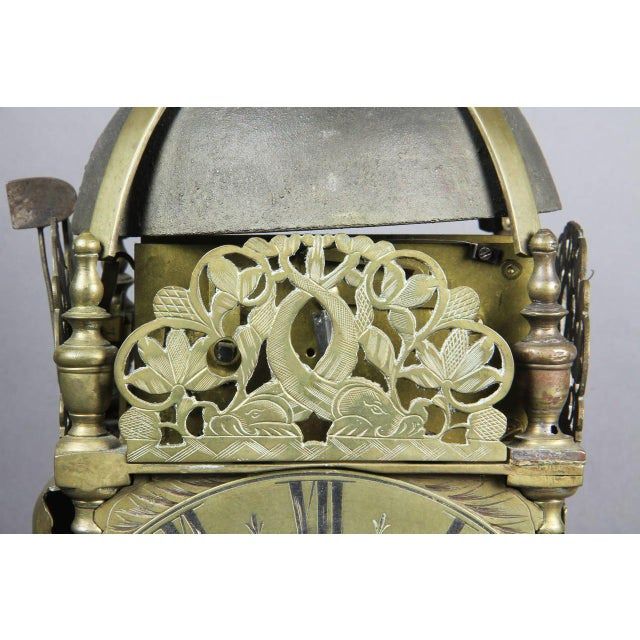 Domed top with bell and finial over dial with pierced decorated crest , bun feet