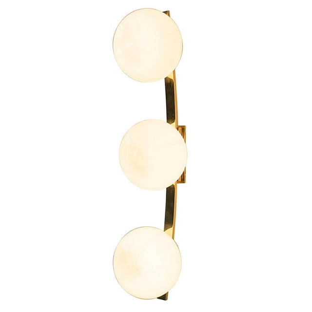 Italian Murano wall light shown in glossy dark gray Murano glass pebbles on curved polished brass frame, designed by Fabio...
