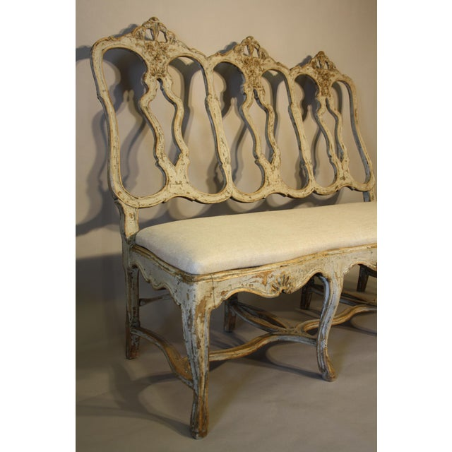 Elegant carved wood Portuguese bench with pale gray paint. Reupholstered seat. 19th frame.