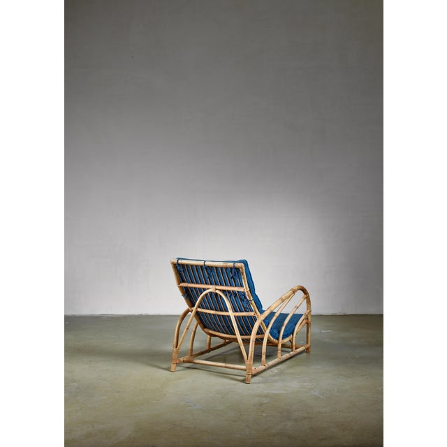 An early Swedish lounge chair made of strong bamboo with rattan connections and a padded blue fabric cushion. Sturdy but...