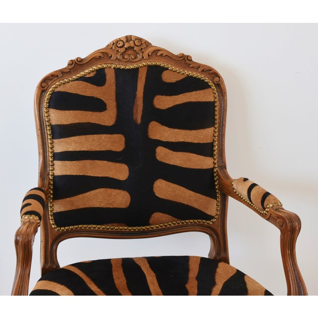 1950s carved walnut wood armchair newly upholstered in professionally stenciled and tanned tiger/zebra patterned striped...
