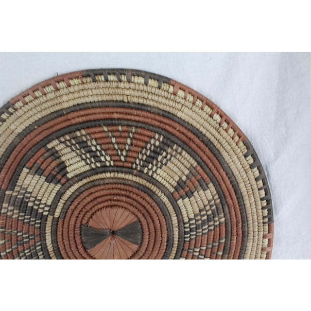 Flat handwoven textile Southwestern tribal platter with varying hues of brown and orange.