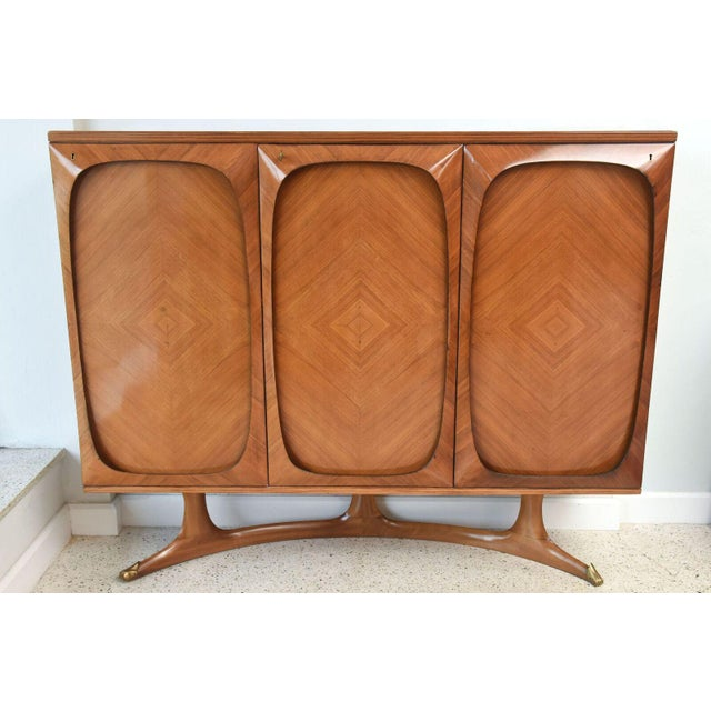 """The glass top above three doors veneered """"au quartre face"""" with a mahogany shaped frame, resting on a """"c"""" shaped stand."""