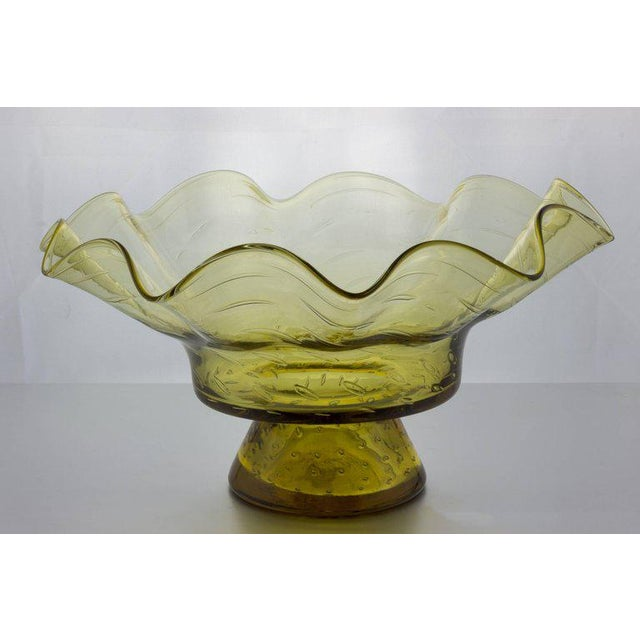 Blench glass bowl in light yellow glass with ruffled design. Measures: 7.5 height x 14.25 diameter.