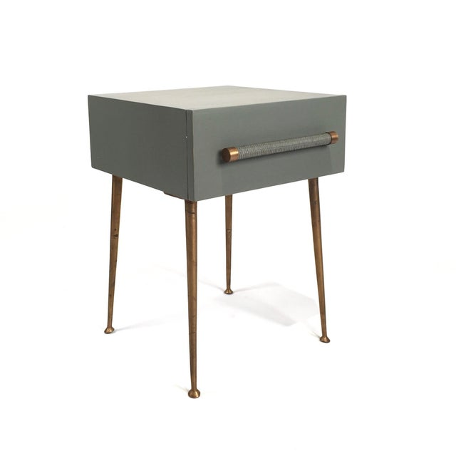This small bedside table features one drawer with a wicker handle, brass trim and is set on four brass legs. Inspiration...