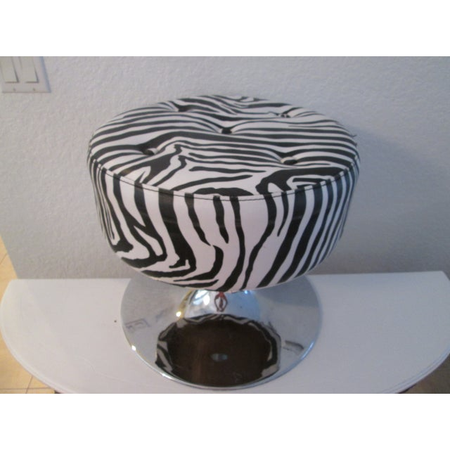 Cool round ottoman/stool features a polished chrome base with cushioned tufted vinyl upholstery in a zebra print pattern....