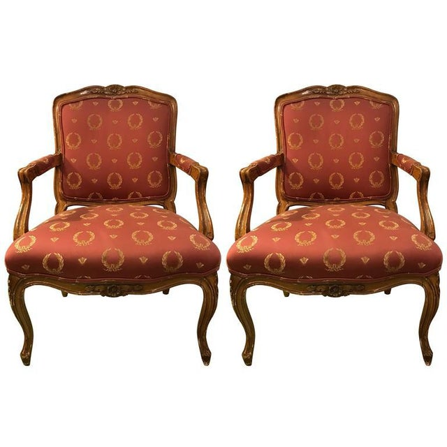 A Pair Of Open Arm Chairs Louis XV Style Feuteuils. A pair of nicely carved frames with rosette decorations on the wood...