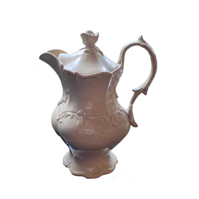 A nicely decorated English Drabware jug with scrolls and a rose top lid. The interior has a built in strainer. It looks as...