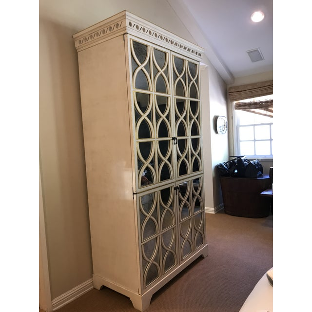 Gorgeous Oly Studio Elisabeth cabinet. Hardwood with four antiqued mirrored doors. Antiqued white finish with gold detail....