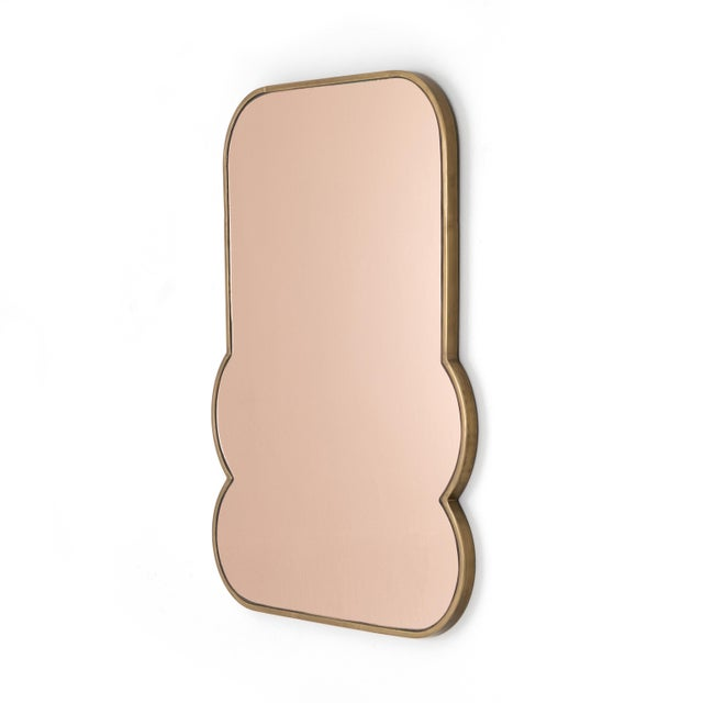 A shapely frame of brass-finished stainless steel welcomes light pink mirrored glass, reflecting style in any space. Great...