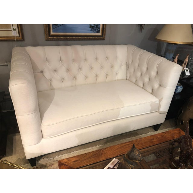 A glamorous tufted loveseat having a box shape, removable single seat cushion and ebonized feet. Measurers: Seat height 19...