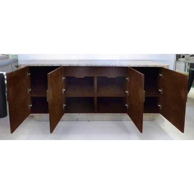 A Mid-century Modern tessellated stone credenza with curved ends and brass trim and handles. The 4 doors open to reveal...