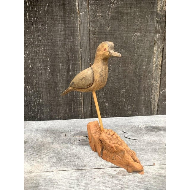 Naive wood carved bird. This primitive bird model can be displayed standing (leans on purpose) or could be hung. The...
