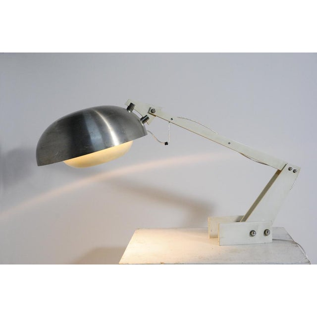 1960's adjustable desk lamp is made of enameled steel and aluminum, spun aluminum, chrome-plated steel. Part painted...