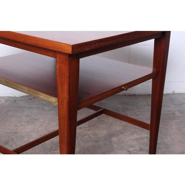 A pair of mahogany tables with slide out shelves. Designed by Paul McCobb for Calvin.