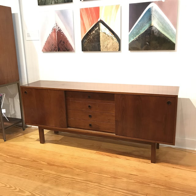 Custom mid-century style credenza handcrafted in Italy from solid walnut. Doors slide open up to adjustable shelving...