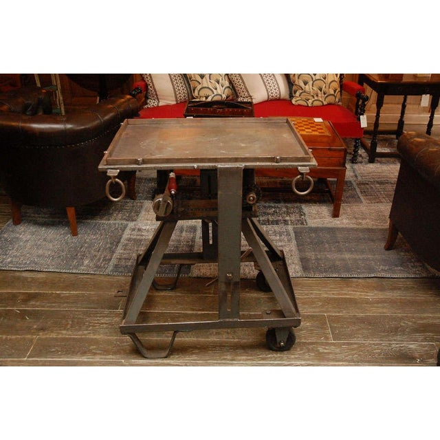 An iron industrial lifting table on wheels with crank mechanism and transport handle. Serves as a side table, stand,...