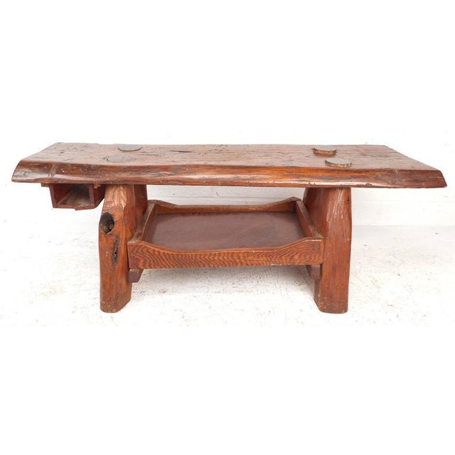 Unique rustic vintage cobbler's bench features a thick tree slab mounted on splayed legs with convenient storage...