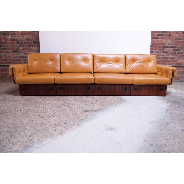 Brazilian low, modular sofa set in rosewood that can form one four-seat sofa, two settees, or a single chair with a three-...
