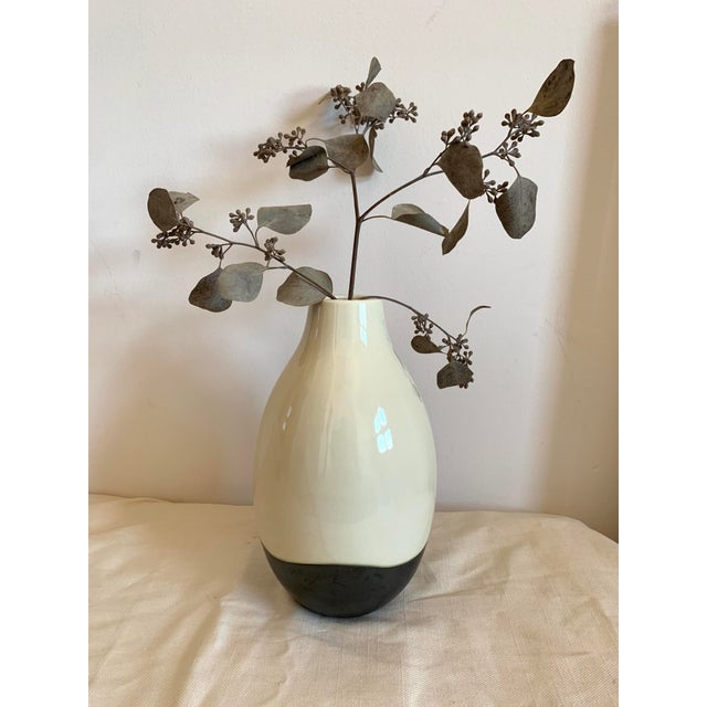 This elegant black and white vase has a modern profile and two-tone charcoal black and cream glaze.