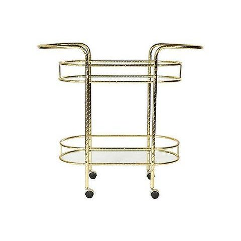 Vintage gilt metal oval rolling bar cart with two glass shelves, circa 1960s. The gilt metal has a swirl design. The...
