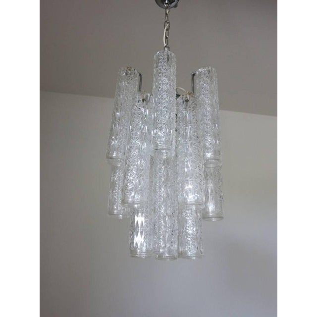 Italian vintage chandelier with clear Murano glass cylinders blown with intricate shaped patterns, mounted on chrome frame...