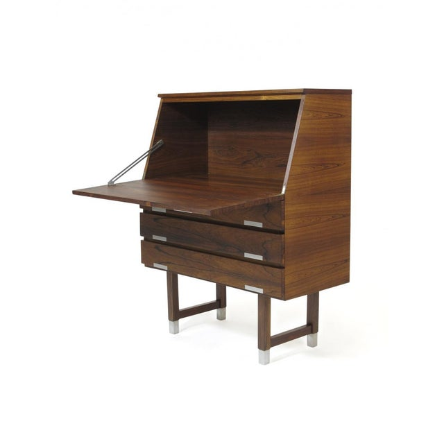 1960's Rosewood secretary desk with drop-front desk over three drawers with aluminum inlay pulls, raised on square legs...