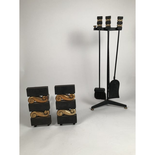 A pair of modernist iron and brass andirons, together with a matching set of fireplace tools on Stand (shovel, brush and...