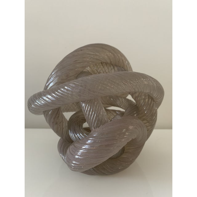 Vintage, thick sculpture depicting an intertwining knotted rope in shimmering, iridescent pinkish glass. Contorted and...
