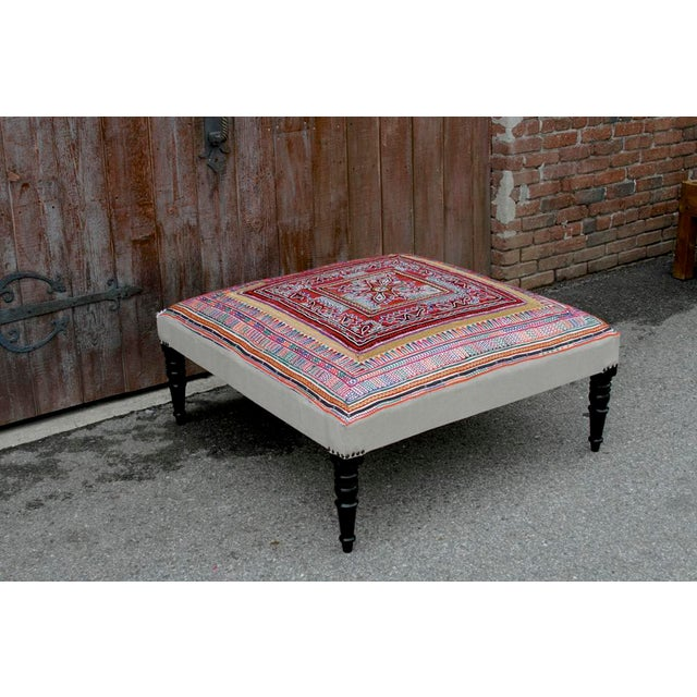 Made with modern designs in mind, this Rabari textile upholstered ottoman stands on ebonized spindle legs accented with...