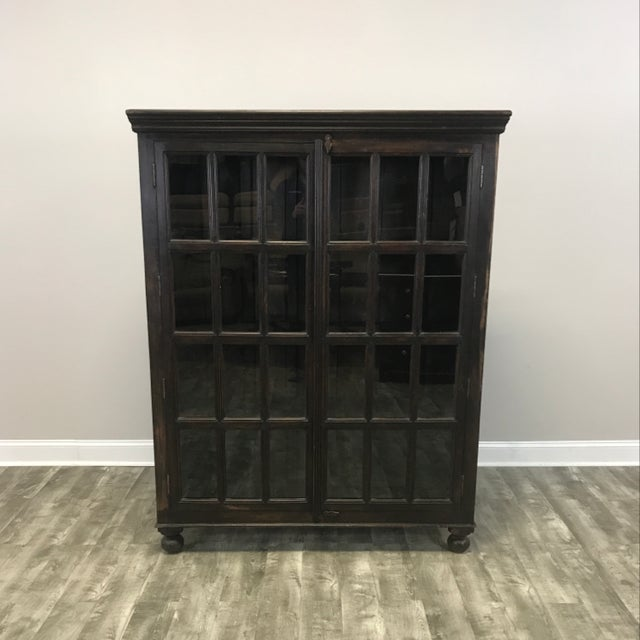 Handcrafted glass-paned storage unit by Crate & Barrel. Double bi-fold doors open to expose four shelves with lots of...