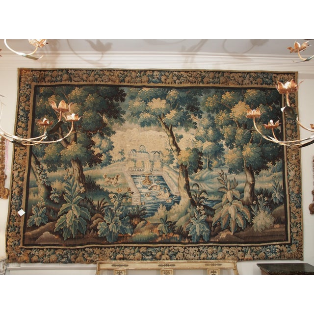 A Franco-Flemish verdure tapestry with a border surrounding a view of a chateau in a park with a pool and fountain in the...