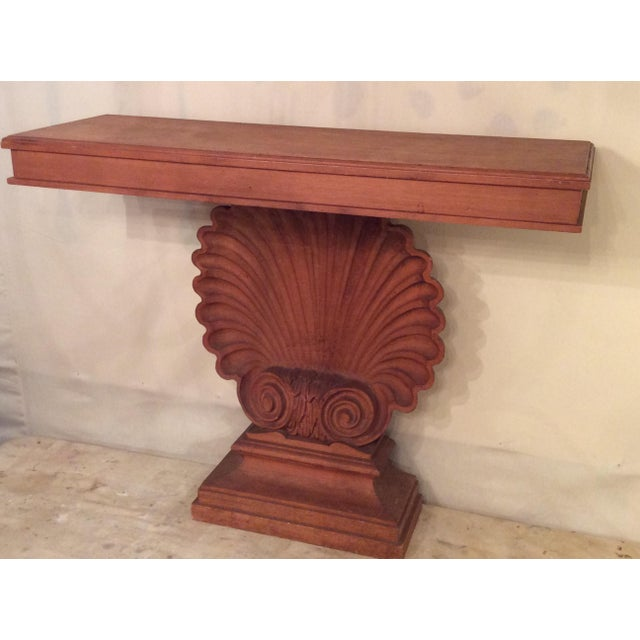 Handsome hall table in mahogany. Huge hand-carved shell base supports a rectangular top. Designed to fit against a wall....