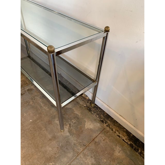 This substantial chrome and glass console table suitable for the entry is made of chrome and glass with brass finials and...