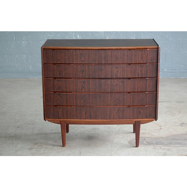 Exquisite 1960s rosewood chest of drawers with five large drawers in bookmatched rosewood veneer. Highest quality...