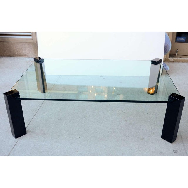 This cocktail table features Black lacquered wood legs supporting an octagonal thick glass top with polished edge details.